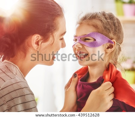 Happy family is preparing for a costume party. Mother and her child girl playing together. Girl in Superman's costume.  - stock photo
