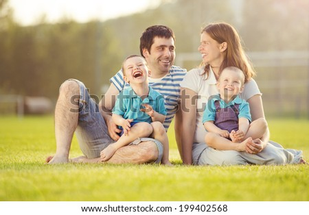 Happy family is relaxing and sitting on football pitch