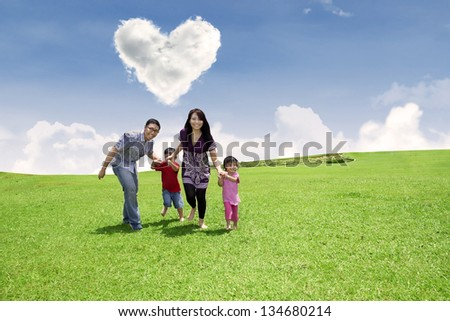 Happy family is running together in the park under heart shape clouds - stock photo