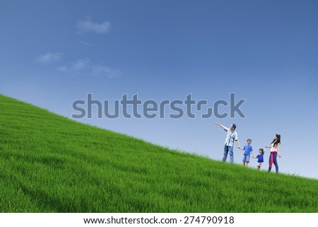 Happy family is walking on green field while holding hands - stock photo