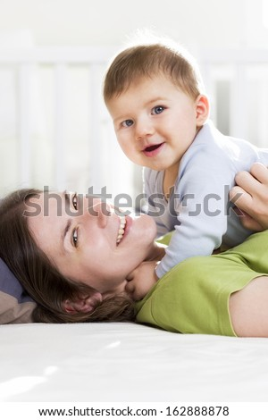 Happy family: Joyful mother and baby boy lying down in bed, laughing and having fun while she is tickling him. - stock photo