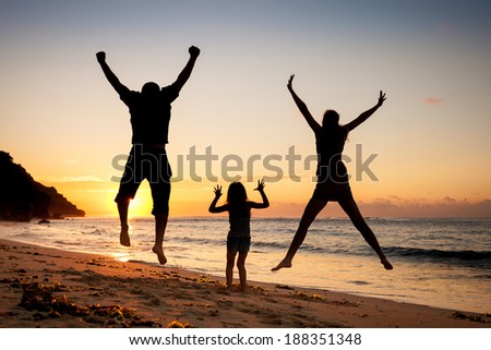 Happy family jumping at the beach in the dawn time
