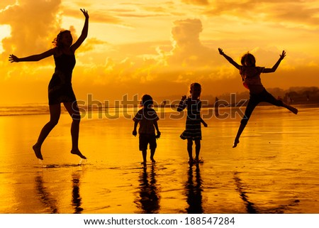 Happy family jumping at the beach in the dawn time - stock photo