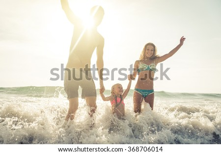 Happy family jumping in the waves, in Karon beach, Phuket. Family enjoying vacations in tropical places. Concept about people and vacations - stock photo