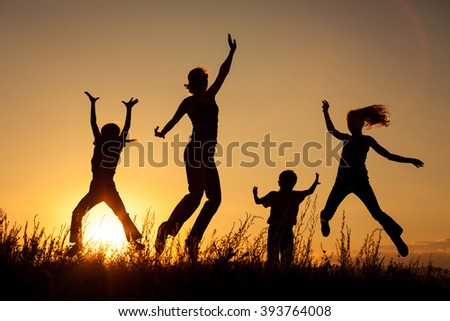 Happy family jumping near the lake at the day time. Concept of friendly family.