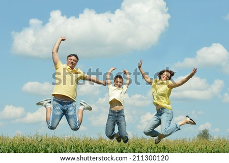 Happy family jumping on field on sky background - stock photo
