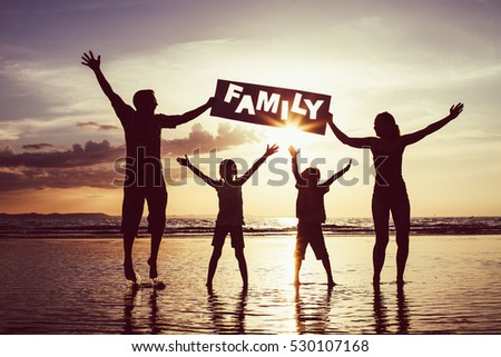 "Happy family jumping on the beach at the sunset time. Parents hold in the hands  inscription ""Family"". Concept of happy family."