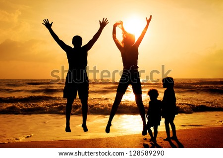 Happy family jumping on the beach on the dawn time - stock photo