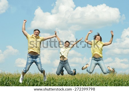 Happy family jumping outdoors against the sky - stock photo