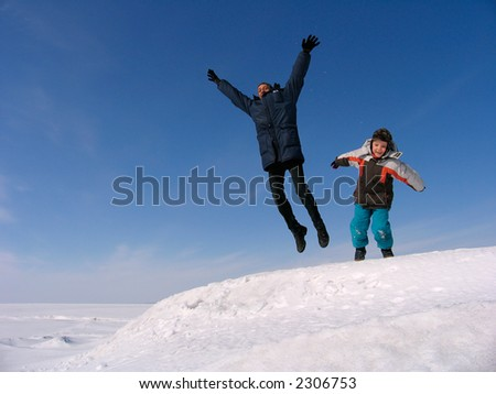 Happy family jumping over snow under blue sky - stock photo