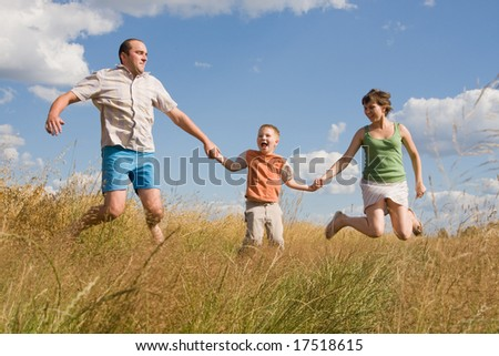 happy family jumping together on a summer day