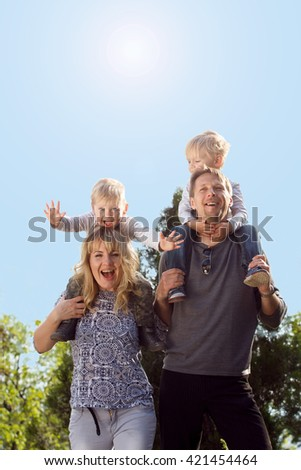Happy family, kids on parents shoulder. Coloring and processing photos in vintage style with soft selective focus