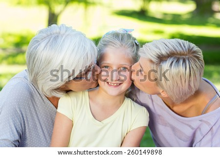 Happy family kissing little girl on a sunny day - stock photo