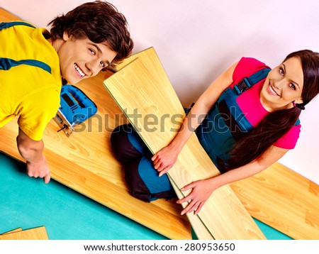 Happy family laying wooden parquet at home. - stock photo