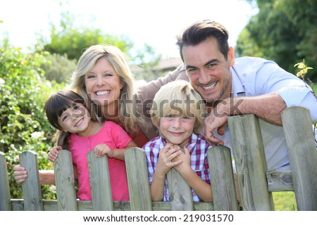 Happy family leaning on fence by country home