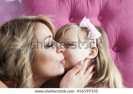 Happy family. Little girl kissing mother - stock photo