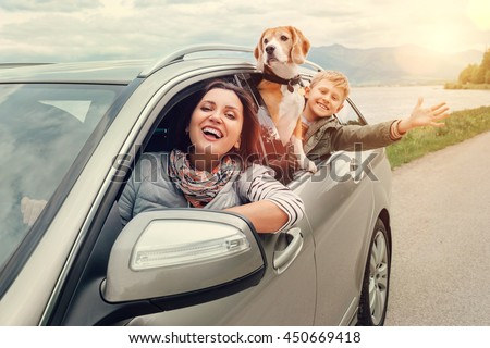 Happy family look out from car windows - stock photo