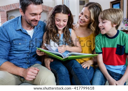 Happy family looking at a photo album at home