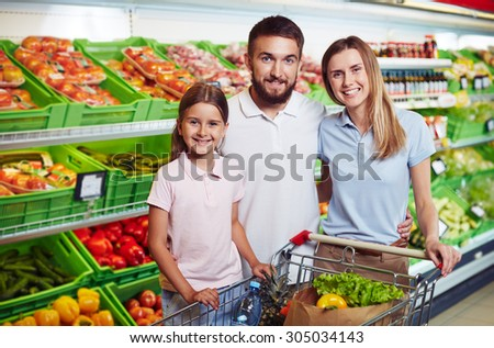 Happy family looking at camera in supermarket