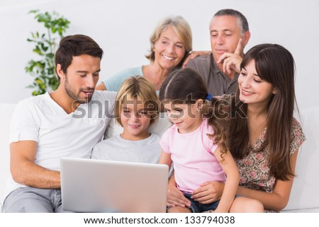 Happy family looking at laptop on the couch - stock photo