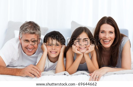 Happy family looking at the camera on their bed