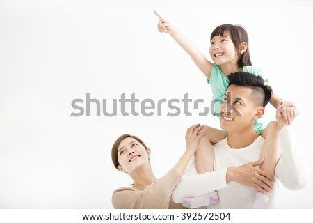 Happy family looking away and pointing - stock photo