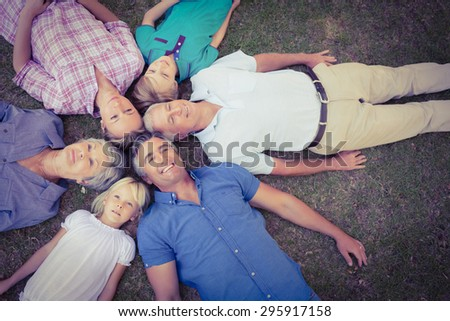 Happy family looking up the camera on a sunny day - stock photo