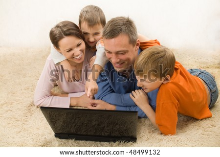 happy family  lying and looking at laptop