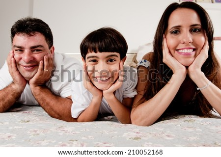 Happy Family lying down in the bed . - stock photo