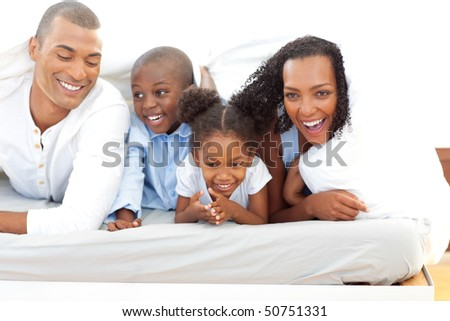 Happy family lying down on bed - stock photo