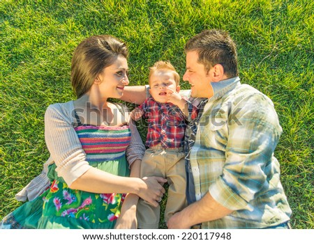 happy family lying down on the grass. Young couple with kid  - stock photo