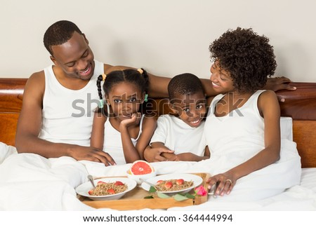 Happy family lying in bed together enjoying breakfast