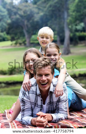 Happy family lying in park on a sunny day - stock photo