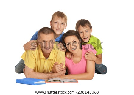 Happy family lying on a floor reading books - stock photo