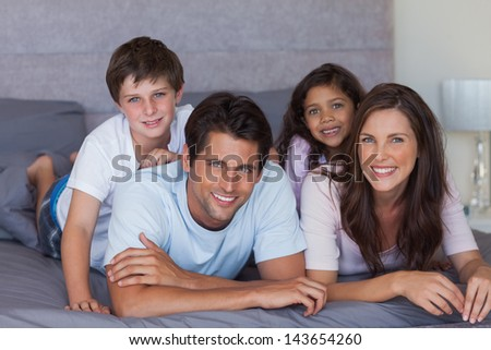 Happy family lying on bed and looking at camera - stock photo