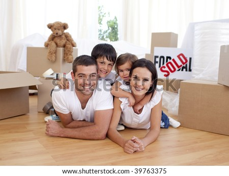 Happy family lying on floor after buying new house - stock photo