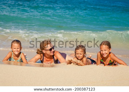 Happy family lying on the beach at the day time
