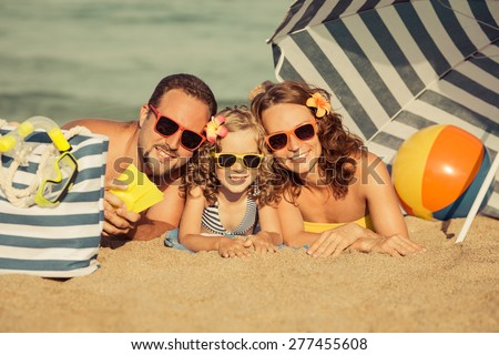 Happy family lying on the beach. Summer vacation concept. Retro toned image - stock photo