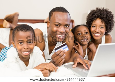 Happy family lying on the bed with laptop