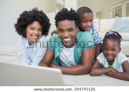 Happy family lying on the floor using laptop at home in the living room