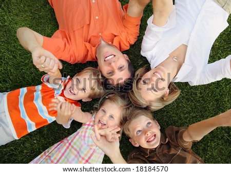 Happy family lying on the grass and holding hands - stock photo