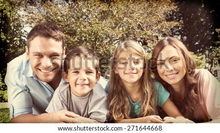 Happy family lying on the grass smiling at camera in park - stock photo