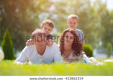 Happy family lying on the green grass. Mom, dad and two sons. - stock photo