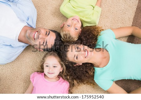 Happy family lying on the rug in a circle at home in living room - stock photo