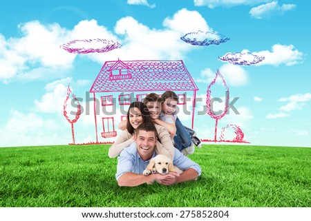 Happy family lying on top of each other with dog against blue sky over green field - stock photo