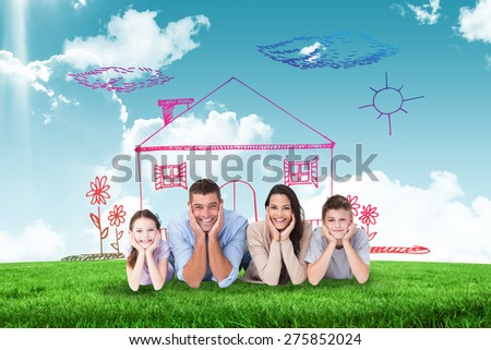 Happy family lying with head in hands against blue sky over green field - stock photo