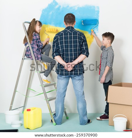 Happy family makes repairs at home. Smiling children painting big Ukrainian flag on wall at home - stock photo