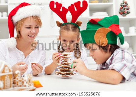 Happy family making a gingerbread cookie christmas tree together