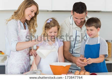 Happy family making cookies together in kitchen - stock photo