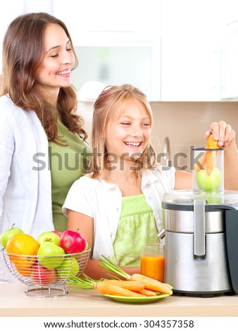Happy Family making fresh apple and carrot juice. Smiling Mother and her daughter Girl drinking fresh carrot and apple juice. Juice Extractor. Healthy eating concept, vitamins. - stock photo